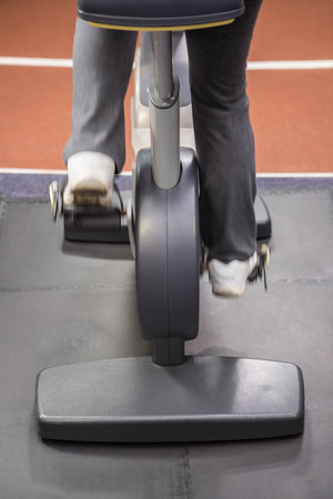 lower section: Lower section of woman on exercise bike at the gym