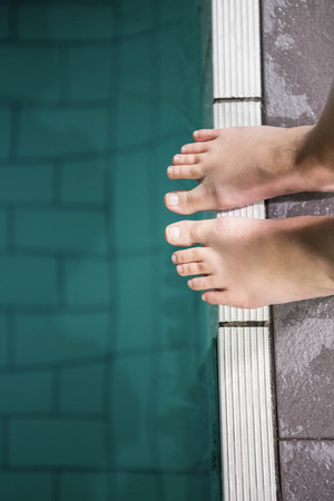 lane marker: Feet of woman standing on the edge of the pool at the leisure center Stock Photo