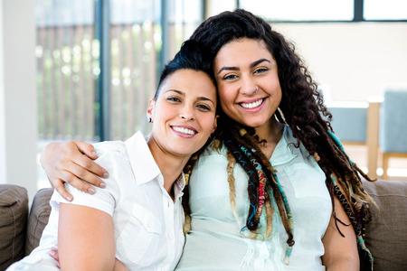 Glimlachend lesbisch paar omarmen en ontspannen op de sofa in de woonkamer Stockfoto