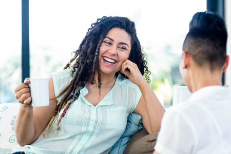 homosexual partners: Lesbian couple smiling while having a cup of coffee Stock Photo