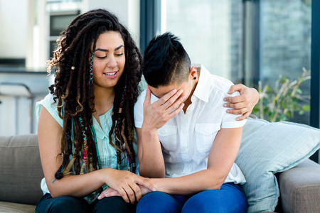consoling: Woman consoling her partner in living room