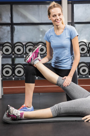 educator: Smiling trainer stretching pregnant womans leg at the gym