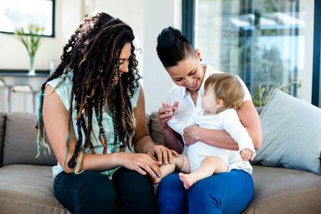 lesbienne: couple de lesbiennes jouant avec leur b�b� dans le salon