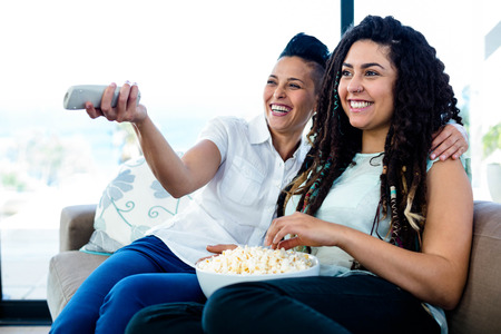 homosexual partners: Lesbian couple sitting on sofa and watching television with a bowl of popcorn Stock Photo