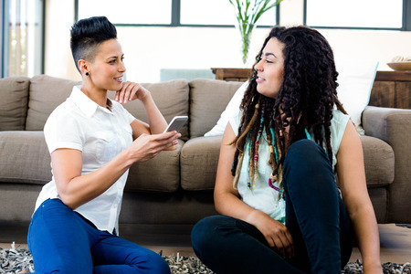 Smiling lesbian couple sitting on rug and looking at mobile phone in living room Stock Photo