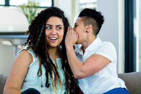 homosexual partners: Lesbian couple whispering in ear and looking surprised