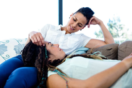 homosexual partners: Woman relaxing on her partners lap in living room