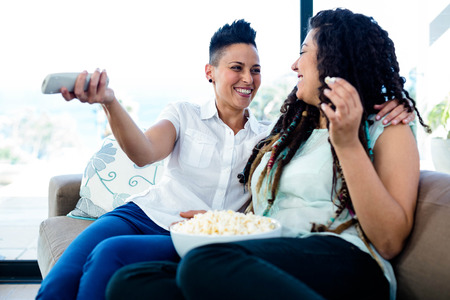 Lesbian couple taking and smiling while watching television