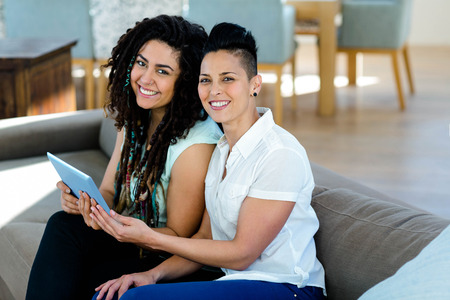 homosexual partners: Lesbian couple using digital tablet in living room