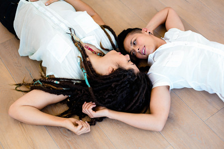 homosexual partners: Lesbian couple in love lying on wooden floor