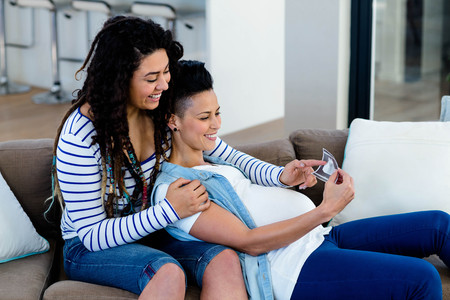 sonography: Pregnant lesbian couple sitting on sofa and looking at sonography report