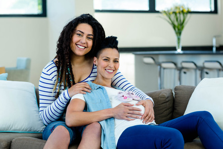 Pregnant lesbian couple sitting on sofa with a pair of pink baby shoes photo