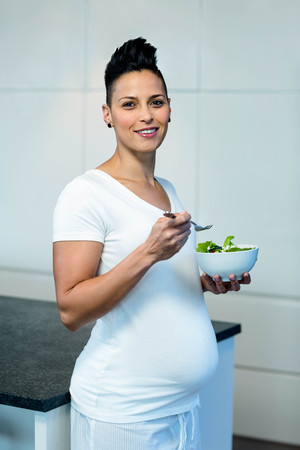Portrait of pregnant woman holding a bowl of salad and smiling photo