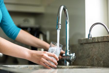 Pretty woman bionda riempire un bicchiere d'acqua a casa