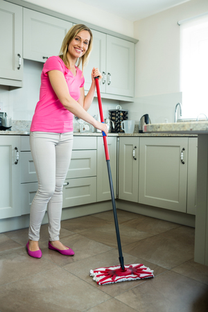 Pretty Blonde Woman Swiping The Kitchen Floor With A Mop Stock Photo ...
