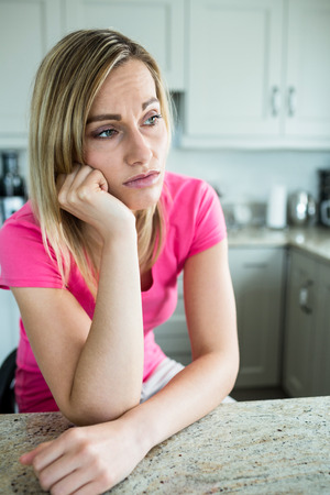 abandonment: Thoughtful blonde woman leaning on her counter in the kitchen