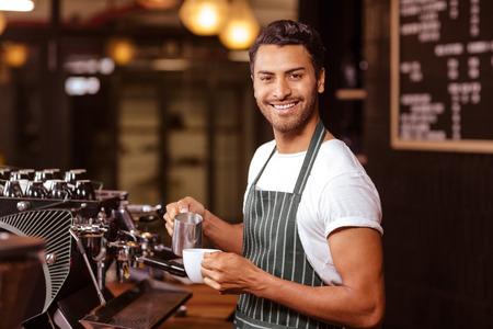 Szép pincér tej hozzáadása a kávét a kávézóban