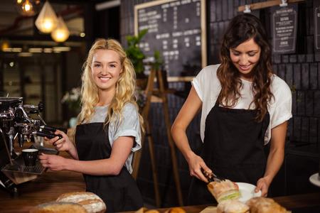 mujer tomando cafe: bastante camareras que trabajan detr�s del mostrador de la cafeter�a Foto de archivo