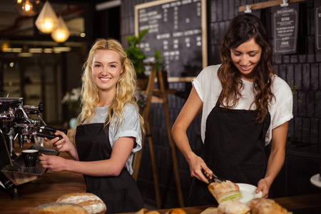 Pretty waitresses behind the counter working at the coffee shop Stock Photo - 52878265