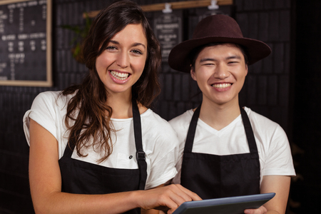 coworkers: Smiling co-workers using tablet at the coffee shop Stock Photo