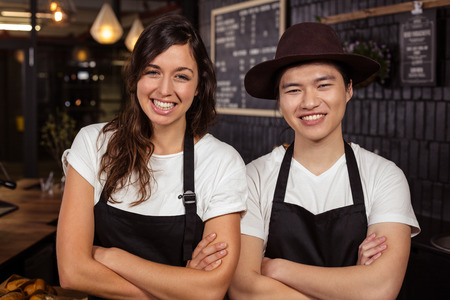 coworkers: Smiling co-workers posing with crossed arms at the coffee shop Stock Photo
