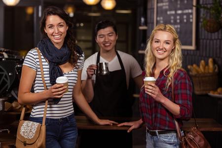 alimentos y bebidas: Sonriendo amigos disfrutando de un café en la cafetería Foto de archivo