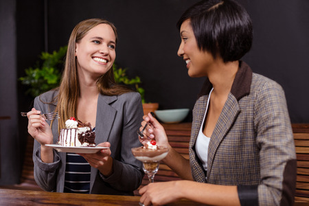 eachother: Pretty women eating desserts in the bar