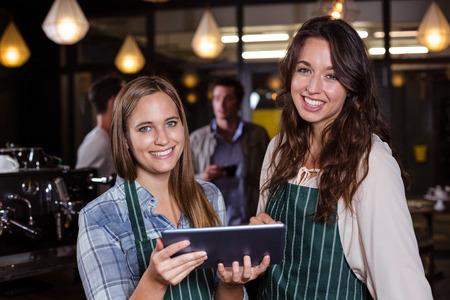 baristas: Pretty baristas using tablet in the bar Stock Photo