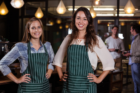 baristas: Pretty baristas standing with hands on hips in the bar Stock Photo