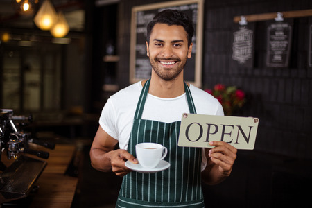 man machine: Smiling barista holding coffee and open sign in the bar Stock Photo