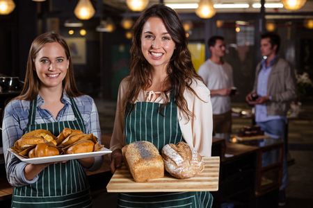 baristas: Smiling baristas holding desserts in the bar