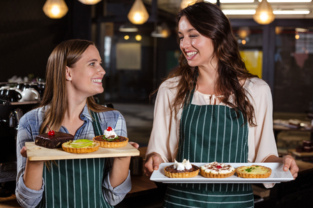 baristas: Pretty baristas holding desserts in the bar Stock Photo