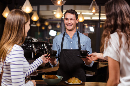 coffees: Smiling barista giving coffees to women at the bar Stock Photo
