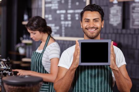 hombre tomando cafe: Sonriendo barista que muestra la tablilla en la cámara en la barra