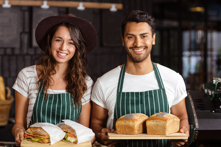 baristas: Smiling baristas holding bread and sandwiches in the bar
