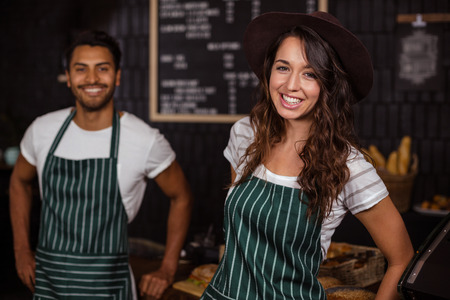 baristas: Smiling baristas looking at the camera in the bar