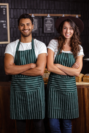 baristas: Smiling baristas standing with arms crossed in the bar