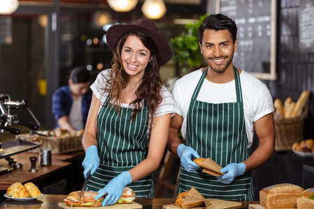 baristas: Smiling baristas preparing sandwiches at the bar