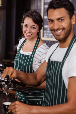 baristas: Smiling baristas working in the bar Stock Photo