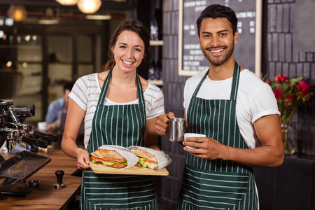 baristas: Smiling baristas holding sandwiches and hot milk in the bar