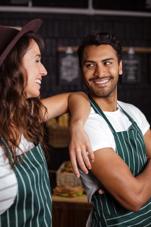 baristas: Smiling baristas looking at each other in the bar