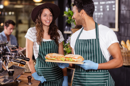 baristas: Smiling baristas holding sandwiches in the bar