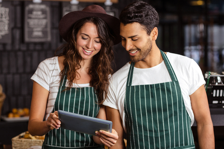baristas: Smiling baristas using tablet in the bar