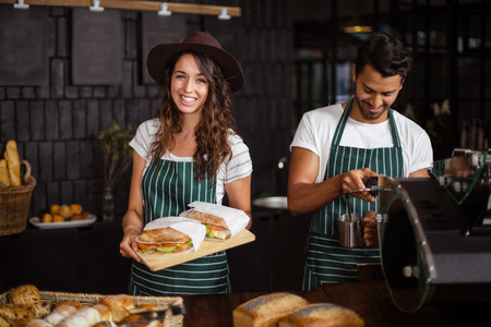 baristas: Smiling baristas holding sandwiches and making coffee in the bar Stock Photo