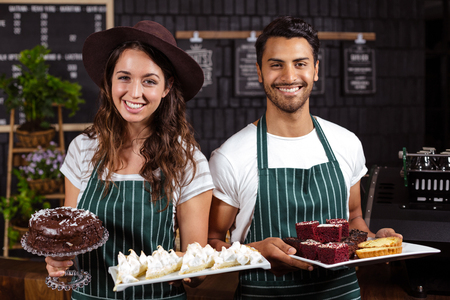 baristas: Smiling baristas holding trays with desserts in the bar Stock Photo