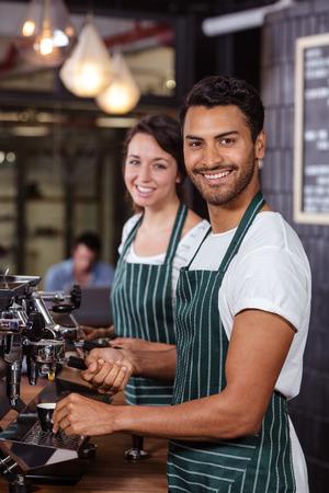 baristas: Smiling baristas using coffee machine in the bar