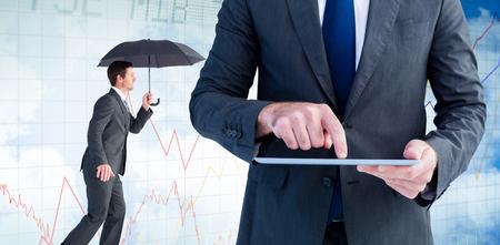 sheltering: Businessman sheltering under black umbrella against stocks and shares