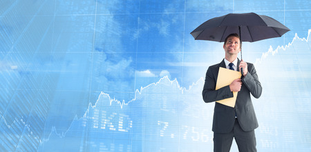 sheltering: Businessman sheltering under umbrella holding file against stocks and shares