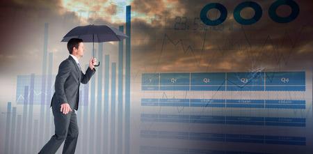 sheltering: Businessman sheltering under black umbrella against blue data