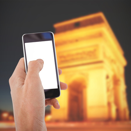 triumphe: Cropped hand of man using mobile phone against arc de triumphe in france